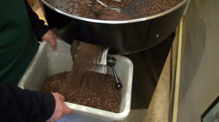 Man roasting coffee beans, machine, coffee beans falling into container Stock Footage