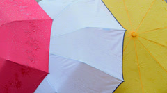Wet colored umbrellas background Stock Footage