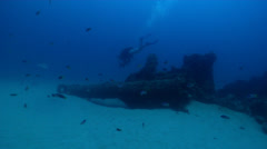 Ocean scenery pans from tech diver across whole wreck, passing diver waves to Stock Footage