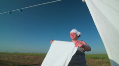 Housewife hanging white laundry on washing line Stock Footage