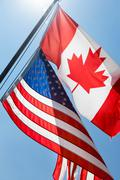 low angle view of canadian and american flags, tobermory, ontario, canada - stock photo