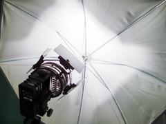 floodlight and reflective umbrella at a film studio - stock photo