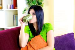Stock Photo of happy woman relaxing drinking herbal tea at home