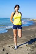 woman holding leg stretching muscles on the beach after jogging - stock photo