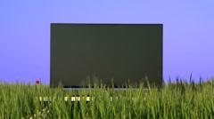 Flat screen TV in the green field Stock Footage
