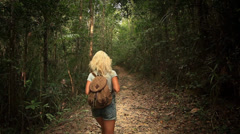 Girl walking near the creek in the jungle Stock Footage