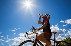 Cyclist resting and drinking isotonic drink. Stock Photos