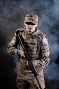 Soldier with a rifle on a black background Stock Photos