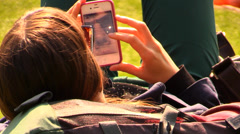Girl at the park touching the screen of her iPhone Stock Footage