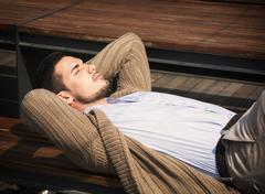 Attractive young man laying down on wood bench Stock Photos