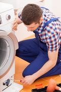 Repairman fixing washing machine Stock Photos