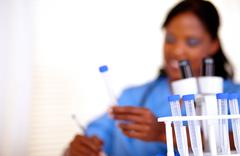 Afro-american nurse working with test tube - stock photo