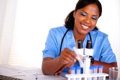 Smiling black nurse working with a test tube Stock Photos