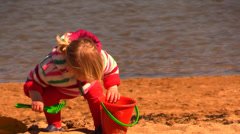 A little girl playing alone at the beach building sand castles Stock Footage