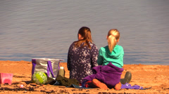 Mom and baby girl on the beach watching the sea Stock Footage