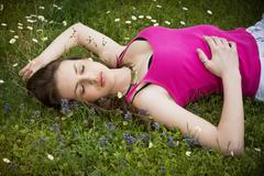 attractive young woman laying down in grassland - stock photo