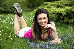 attractive young woman laying down in grassland, casual dress - stock photo