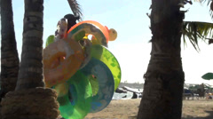 Unknown man passes carrying tons of floaty toys on a beach Stock Footage