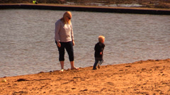 Mom and son running on the beach Stock Footage