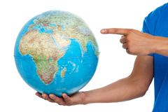 A finger pointing at the globe. closeup shot - stock photo
