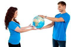 Causal young couple holding globe together - stock photo