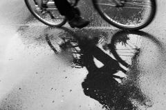 Cyclist reflected in puddle in the rain Stock Photos