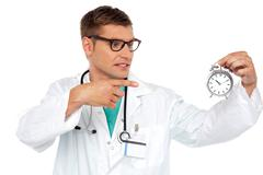 Shocking young doctor pointing at alarm clock - stock photo