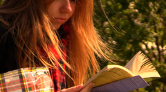A romantic girl reading a book at the park (original speed) Stock Footage