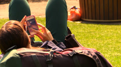 Girl lying at the park touching the screen of her iPhone - stock footage
