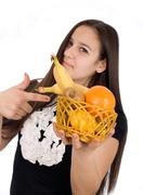 Beautiful girl holds out a basket of citrus fruit Stock Photos