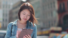 Young Asian woman using iPad tablet pc computer in a city - stock footage