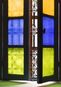 Window with colored glass and arabic grill in marrakesh Stock Photos