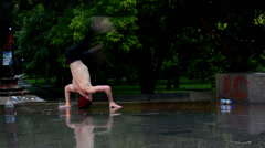 Breakdancer turns his head in the rain in Prague Stock Footage