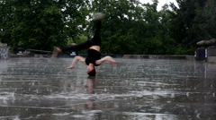Breakdancer dancing breakdance in the rain in Prague - stock footage