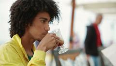 Man drinking coffee in an outdoor cafe Stock Footage