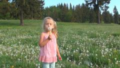 Happy Little Girl Blowing Dandelion on Meadow, Mountains, Child Playing Flowers Stock Footage