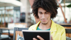 Cute male african college student using tablet computer Stock Footage