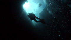 Group of scuba divers descending on deep water wall and cavern tunnel in Palau Stock Footage