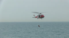 Coastguard rescue helicopter winching up Stock Footage
