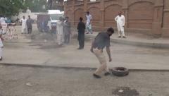 Police man kicking burning tire in Peshawar, Pakistan Stock Footage