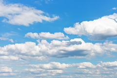 White fluffy clouds in blue sky Stock Photos