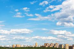 Urban street under blue sky with fluffy clouds Stock Photos