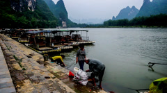 The local people do washing in the Li river, Yangshuo, Guangxi, China Stock Footage