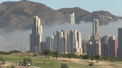 view across golf course to sea fog and skyscraper buildings in beni - stock footage
