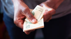 Close up of a african american person counting 10 dollars bills - stock footage