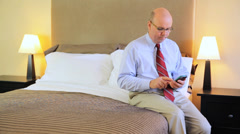 Mature Business Man Using A Smartphone iPhone Sat On A Hotel Bed Stock Footage