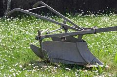 sturdy bit of ancient iron plow for plowing the land - stock photo