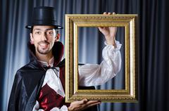 Stock Photo of Magician with photoframe in studio
