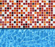 Stock Photo of red mosaic pavement with pool background