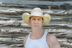 Cowboy in front of a log cabin Stock Photos